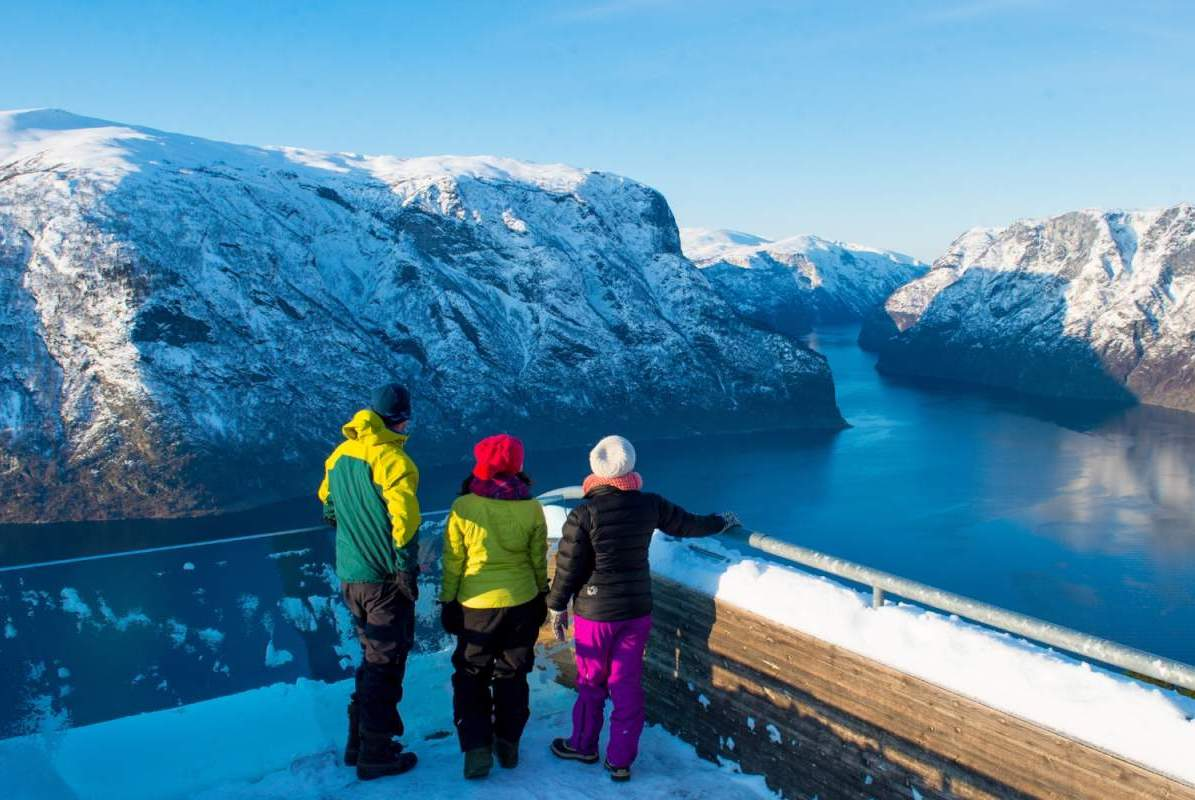 A family stands enraptured by the massive fjord and the surrounding mountains on their Norway luxury holiday in Sognefjord
