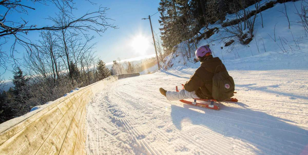 A child rides a toboggan down a snow-covered slope on their Norway luxury holiday