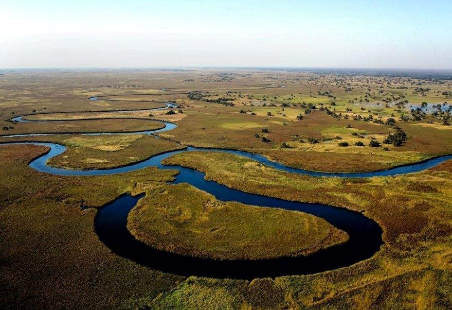 The winding blue Okavango River cuts through the great African savannah