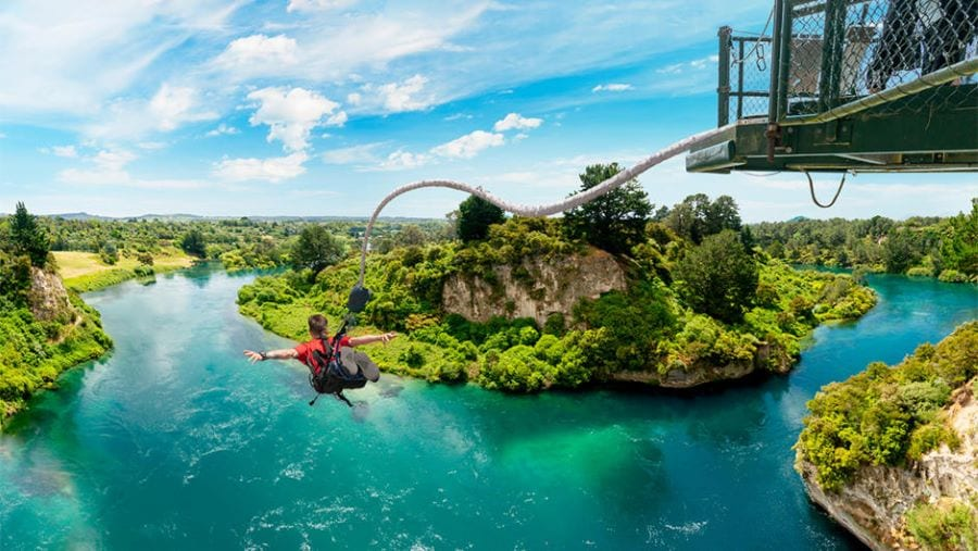 Jumping over a panoramic landscape of a lake surrounded by greenery is a perfect way to kick off your Oceania luxury travels!