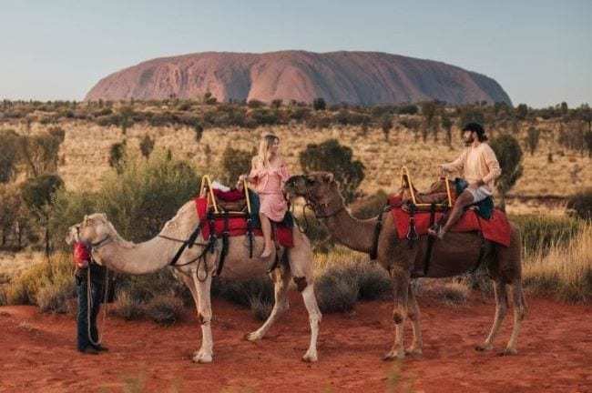 A couple takes a ride around Ayers Rock atop camels on their luxury Australia travel