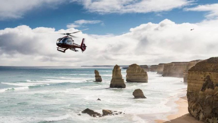 A helicopter soars over the remaining 12 Apostles rock formations in Australia