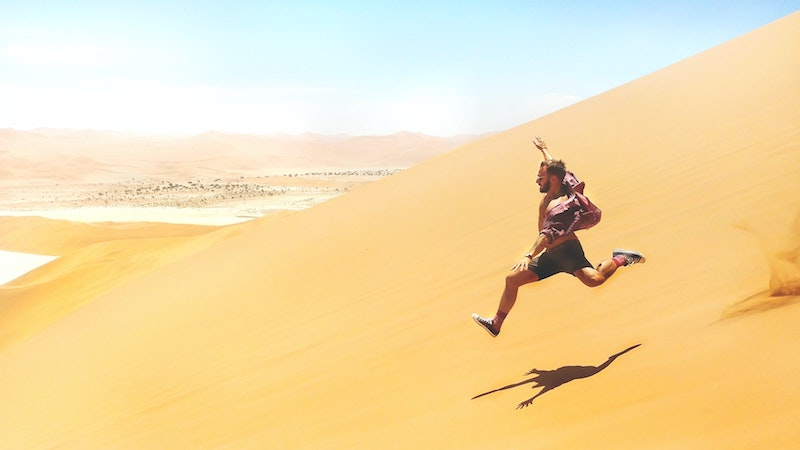 A tourist having a jumping good time at the Sossusvlei sand dunes, basking under the glow of the sun.