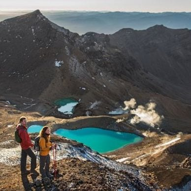 Hikers admire a mountainous scenery overlooking azure craters of water