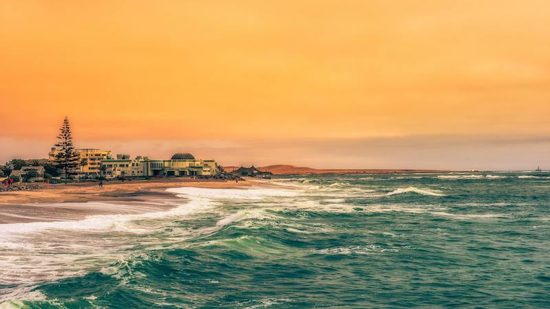 As the sun sets over the coastal town of Swakopmund in Namibia, the sea and the town are painted in a brilliant orange hue, a beautiful scenery for tourists on their luxury Namibia travels