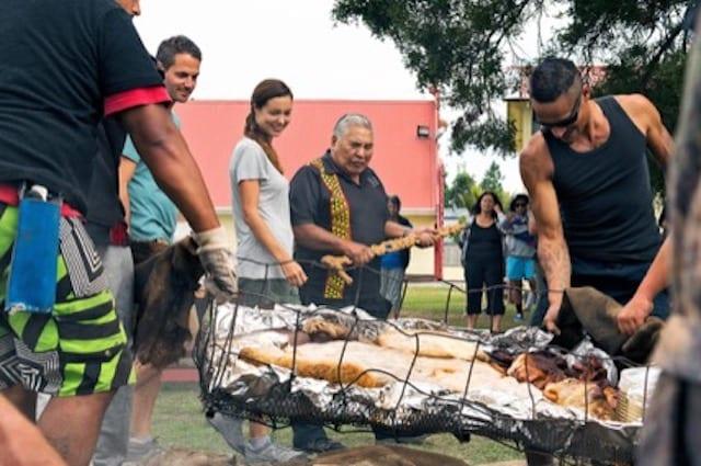 Tourists and Maori gather around the roast, waiting to feast on the traditional Maori Hangi