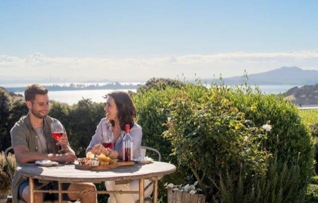 A couple enjoys a glass of red wine in the amazing scenery of Waiheke Island on their luxury New Zealand holiday