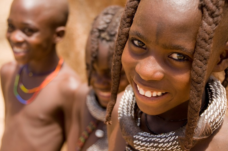 The children of the Himba tribe with their distinctive red ointment on their skin and wearing their hand-made jewellery