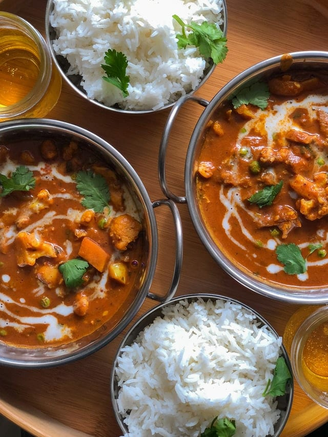 Bowls of spicy and fragrant Indian curry served together with aromatic Briyani rice, a perfect gourmet delight on a Asian luxury travel