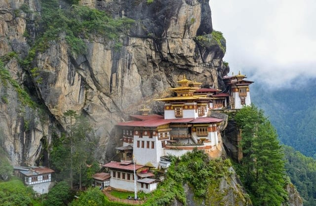 A temple sits serenely on a cliff, astounding visitors on their Bhutan luxury travel.