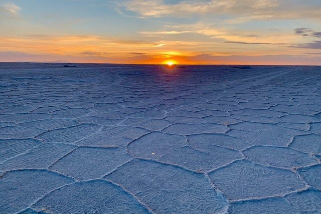 The sun sets over the white salt-formed Salar de Uyuni, illuminating naturally-formed shapes on the ground
