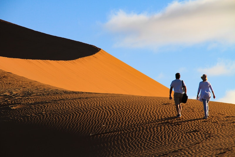 A couple treks up the red dunes of Sossusvlei in the Namib Desert during their luxury travel to Namibia