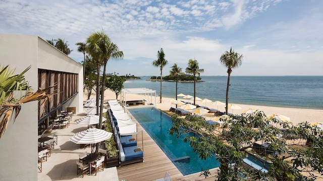 A picture of relaxing serenity: sun-loungers, a swimming pool overlooking the sea and a place to sit and dine