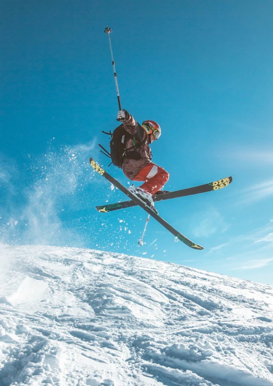 A skiier performing tricks in mid-air down a snowy slope, a treat for everyone in Hokkaido during their Japan luxury travels