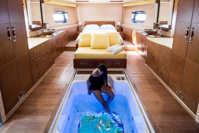 A woman watches fish swim beneath her feet in her glass-bottomed tub aboard her luxury yacht, Soneva in Aqua!