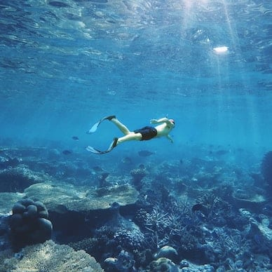 A man free-dives amongst the corals and fish in the sparkling sapphire waters of the Indian Ocean