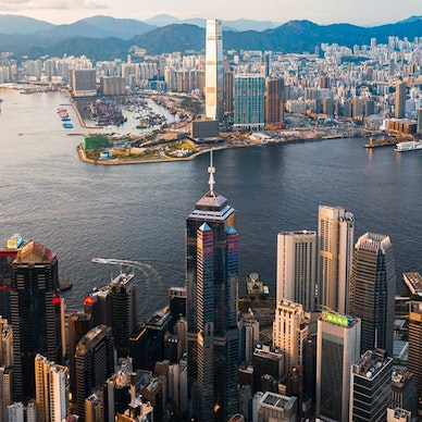 An aerial view of the entire Hong Kong city skyline, the blue mountains in the backdrop and the glistening waters of the Victoria Harbour