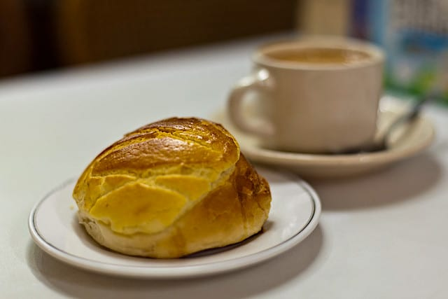 Pineapple bread, a popular snack among locals, is accompanied by a cup of tea in a local coffeeshop