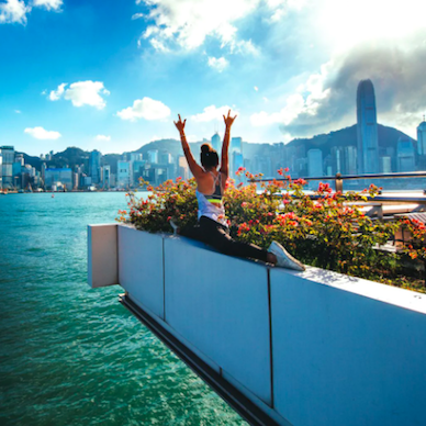A woman stretching above Victoria Harbour, with Hong Kong city skyline in the background.