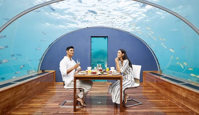 A couple enjoy a magical romantic meal under the sea, with sharks and fish swimming overhead.