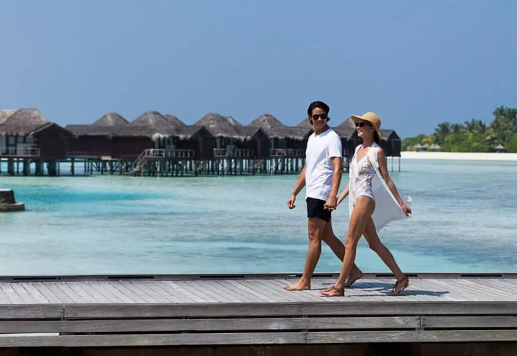 A couple strolls on a jetty in Anantara Veli Maldives, having some great private time together.