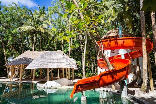 An eye-catching red slide accompanies your island villa in Maldives when you stay at Soneva Fushi island resort.